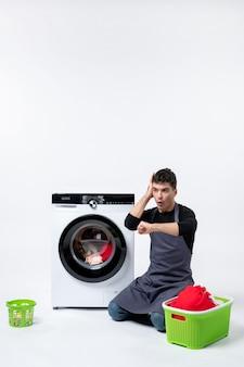 Vista frontal del hombre joven esperando hasta el final del lavado de ropa en la pared blanca