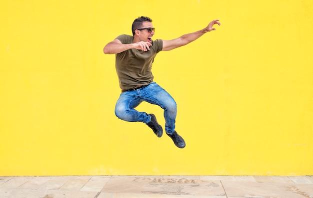 Vista frontal de un hombre joven con gafas de sol saltando contra una pared amarilla brillante en un día soleado