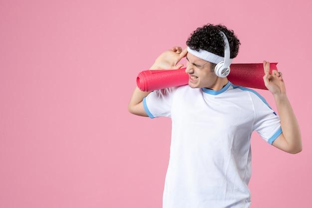 Vista frontal del hombre joven gritando en ropa deportiva con estera de yoga