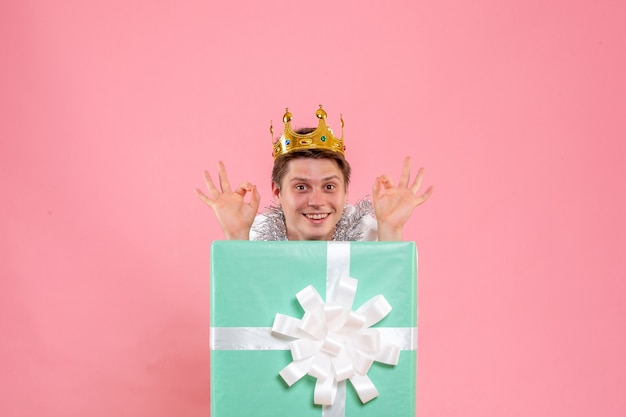 Vista frontal del hombre joven en el interior presente con corona en el piso rosa dormir color emoción navideña fiesta de pijamas