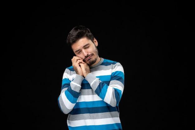 Vista frontal del hombre joven en jersey de rayas azules que se siente triste y llorando