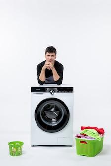 Vista frontal del hombre joven con lavadora y ropa sucia en la pared blanca