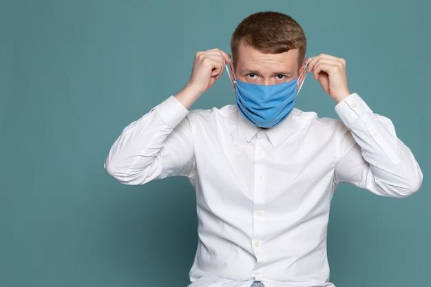 Una vista frontal hombre joven con máscara azul en camisa blanca sobre el escritorio azul