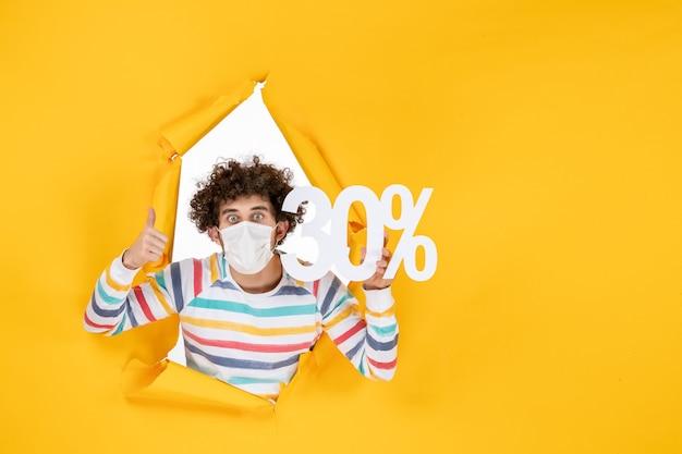 Vista frontal del hombre joven en máscara sosteniendo en color amarillo virus de compras salud covid- foto pandemia