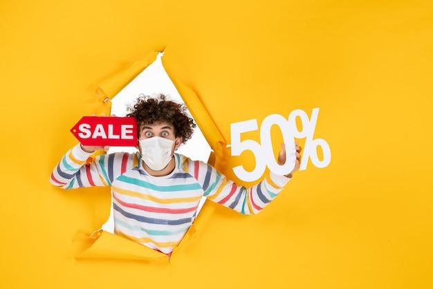 Vista frontal del hombre joven en máscara sosteniendo la escritura sobre el virus amarillo covid de compras- fotos venta pandemia de salud de color