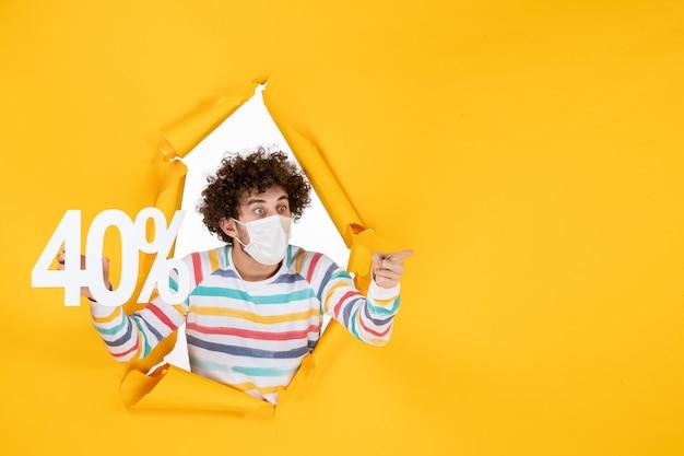 Vista frontal del hombre joven con máscara sosteniendo la escritura sobre el virus amarillo pandemia compras salud covid