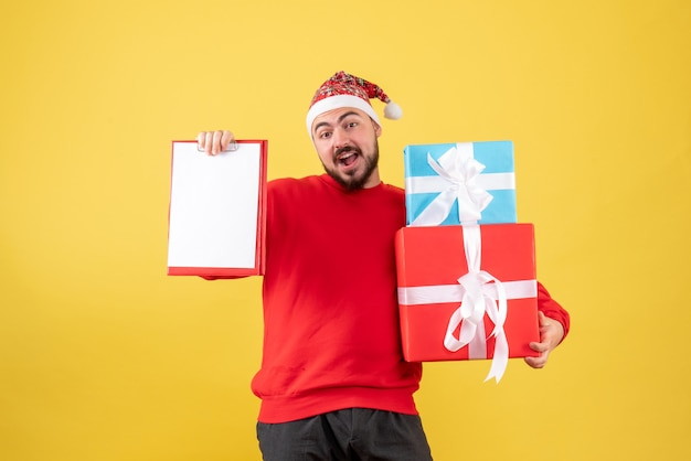 Vista frontal del hombre joven con presente de navidad y nota sobre fondo amarillo