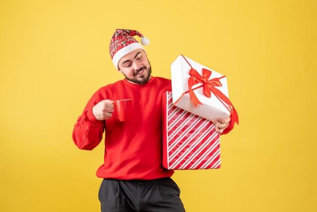 Vista frontal del hombre joven con regalo de navidad y taza de té sobre fondo amarillo