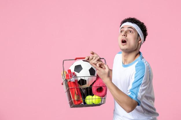 Vista frontal hombre joven en ropa deportiva con canasta llena de cosas deportivas pared rosa