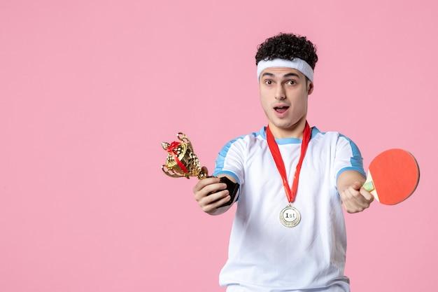 Vista frontal del hombre joven en ropa deportiva con medalla y copa de oro en la pared rosa