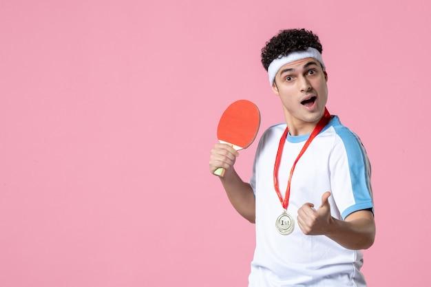 Vista frontal del hombre joven en ropa deportiva con raqueta y medalla en la pared rosa