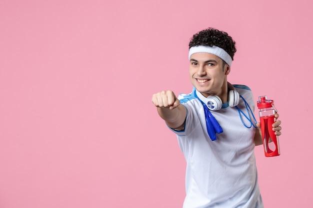 Vista frontal del hombre joven en ropa deportiva con saltar la cuerda alrededor de su cuello pared rosa