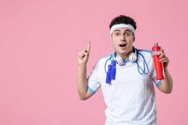 Vista frontal del hombre joven en ropa deportiva con saltar la cuerda y la pared de color rosa agua