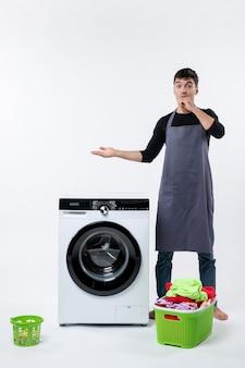 Vista frontal del hombre joven con ropa sucia y lavadora en la pared blanca