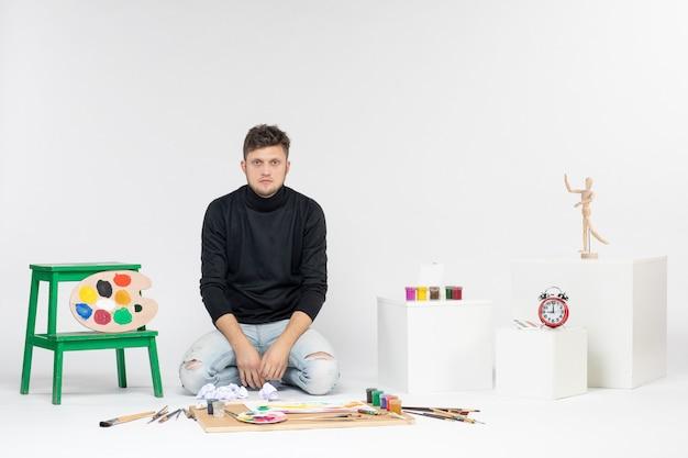 Vista frontal hombre joven sentado alrededor de pinturas y borlas para dibujar en la pared blanca servicio pintura arte artista dibujo dinero entrega de color