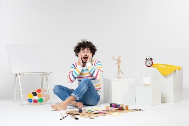 Vista frontal del hombre joven sentado alrededor de pinturas y dibujos en la pared blanca