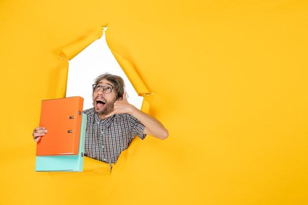 Vista frontal del hombre joven sosteniendo archivos en la pared amarilla