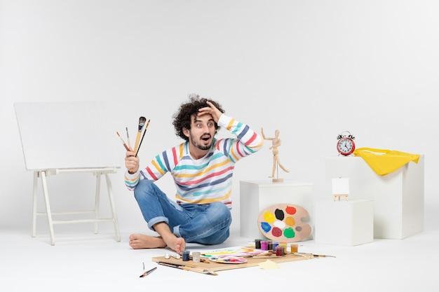 Vista frontal del hombre joven sosteniendo borlas para dibujar en la pared blanca