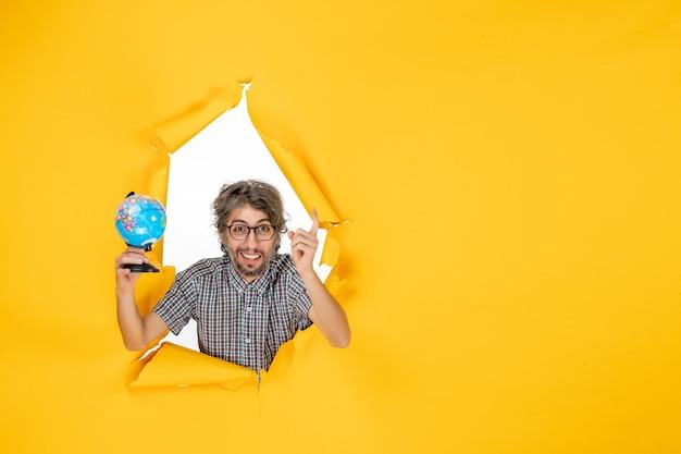 Vista frontal del hombre joven sosteniendo el globo terráqueo en la pared amarilla