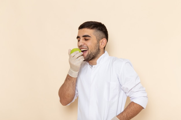 Vista frontal hombre joven en traje blanco con guantes mordiendo manzana en beige