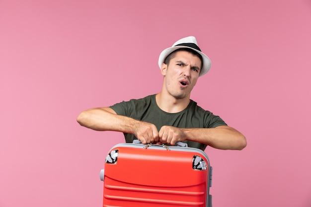 Vista frontal del hombre joven en vacaciones con bolsa roja en el espacio rosa