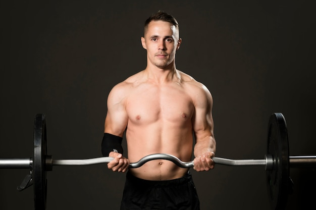 Vista frontal hombre levantamiento de pesas en el gimnasio