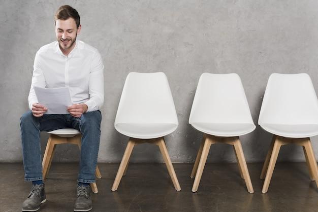 Vista frontal del hombre leyendo su currículum antes de tener su entrevista de trabajo