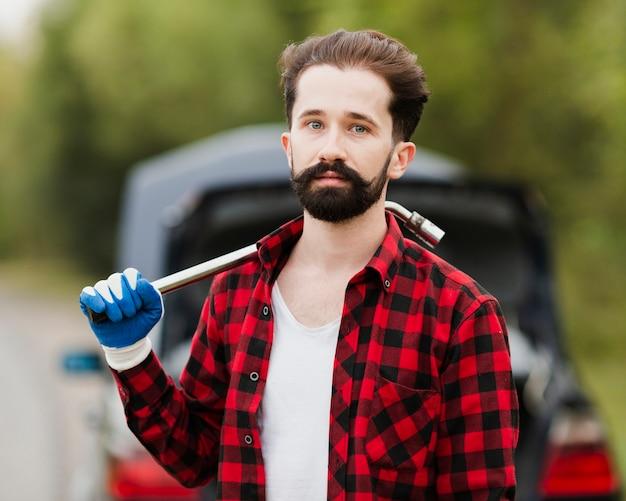 Vista frontal del hombre con llave de neumático