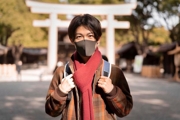 Vista frontal del hombre con máscara en la ciudad.