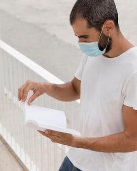 Vista frontal del hombre con máscara médica junto al lago sosteniendo y leyendo el libro