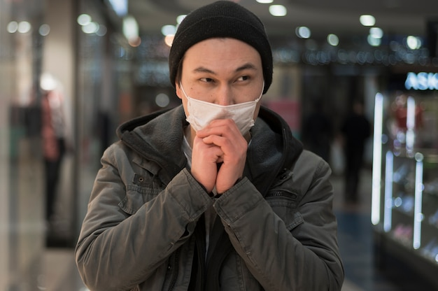 Vista frontal del hombre con máscara médica rezando en el centro comercial