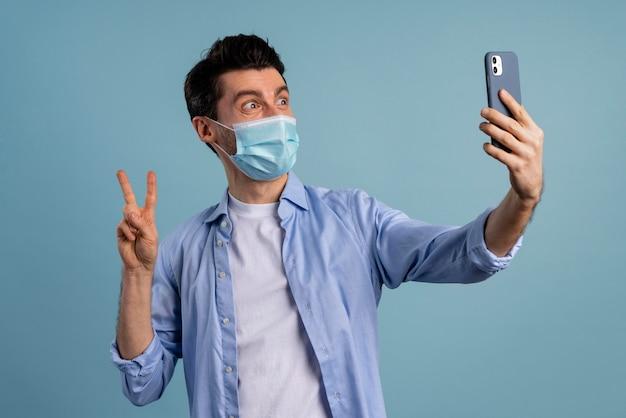 Vista frontal del hombre con máscara médica y tomando selfie mientras hace el signo de la paz