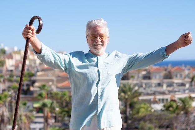 Vista frontal del hombre mayor de pelo blanco al aire libre sosteniendo un bastón. horizonte sobre el agua