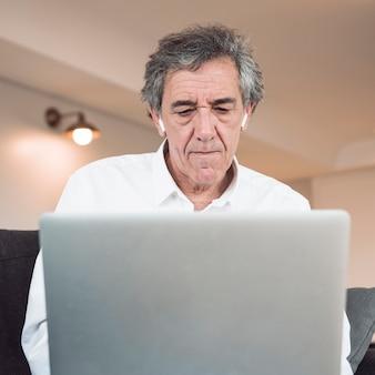 Vista frontal del hombre mayor que usa la computadora portátil con el auricular del bluetooth en sus oídos
