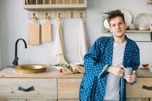 Vista frontal del hombre mirando a la cámara sosteniendo una taza de café en la cocina