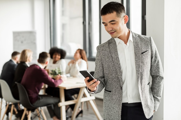 Vista frontal del hombre mirando su teléfono