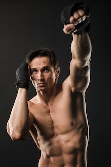 Vista frontal del hombre musculoso sin camisa con guantes de boxeo