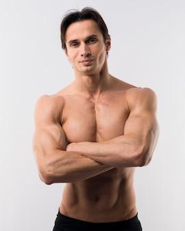 Vista frontal del hombre musculoso posando con los brazos cruzados