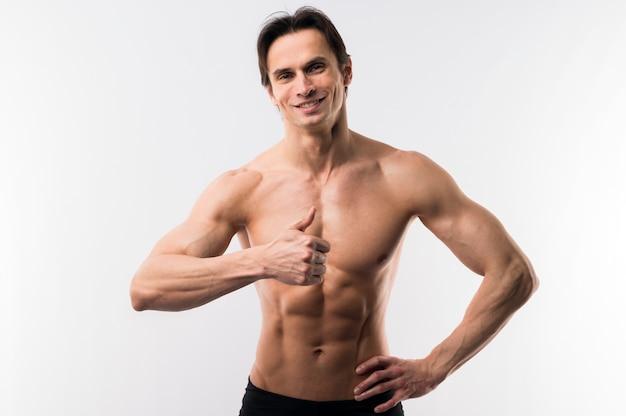 Vista frontal del hombre musculoso posando mientras da pulgares arriba