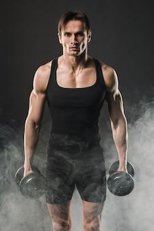 Vista frontal del hombre musculoso posando con pesas en humo