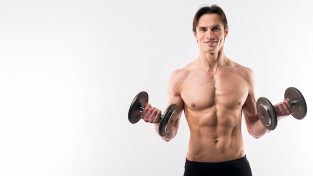 Vista frontal del hombre musculoso sosteniendo pesas con espacio de copia