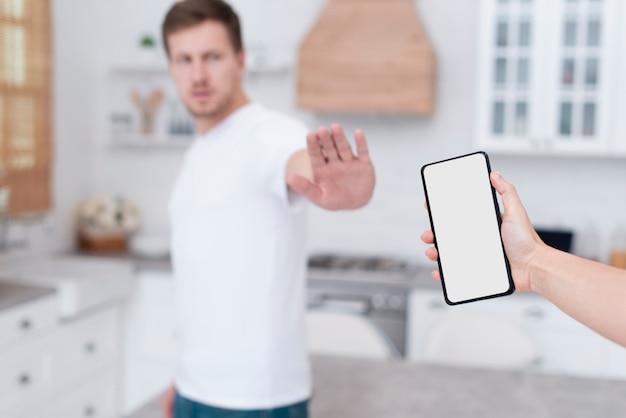 Vista frontal hombre negándose a sostener un teléfono