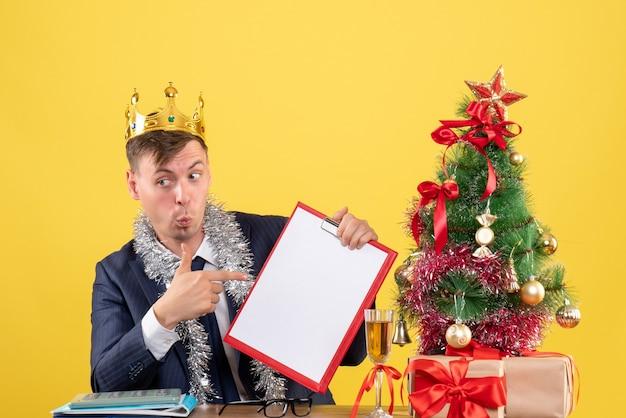 Vista frontal del hombre de negocios apuntando al portapapeles sentado en la mesa cerca del árbol de navidad y presenta en amarillo