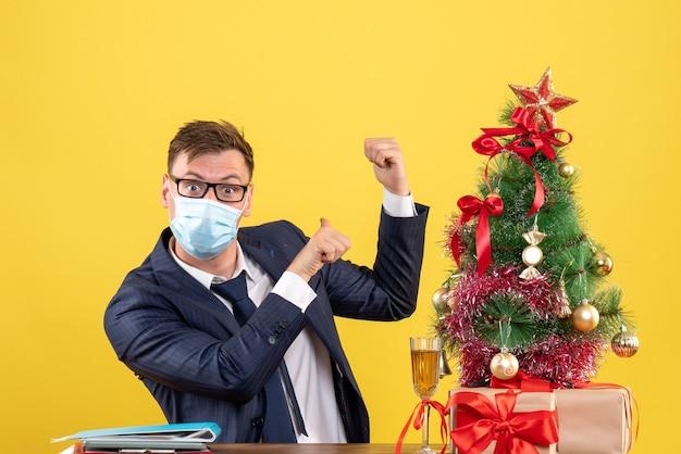 Vista frontal del hombre de negocios apuntando hacia atrás sentado en la mesa cerca del árbol de navidad y presenta en amarillo