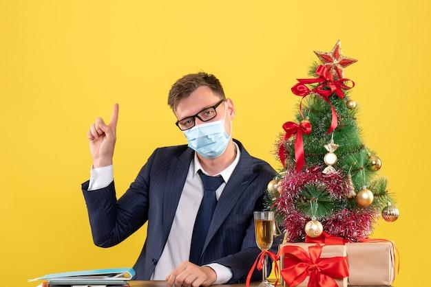 Vista frontal del hombre de negocios apuntando con el dedo hacia atrás sentado en la mesa cerca del árbol de navidad y presenta en amarillo