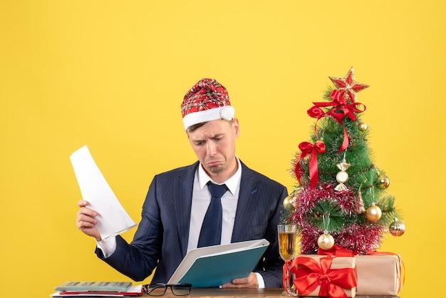 Vista frontal del hombre de negocios confundido sentado en la mesa cerca del árbol de navidad y presenta en amarillo