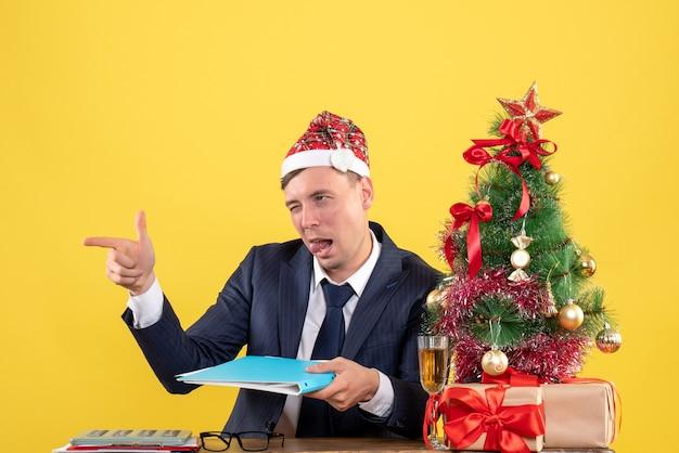 Vista frontal del hombre de negocios con el dedo parpadeando apuntando a alguien sentado en la mesa cerca del árbol de navidad y presenta en amarillo