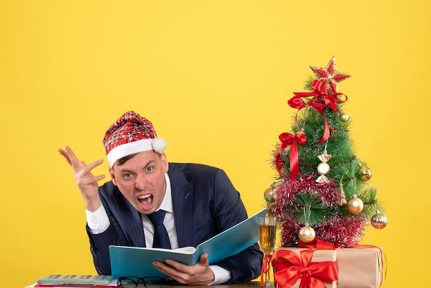 Vista frontal del hombre de negocios enojado con gorro de papá noel sentado en la mesa cerca del árbol de navidad y presenta sobre fondo amarillo