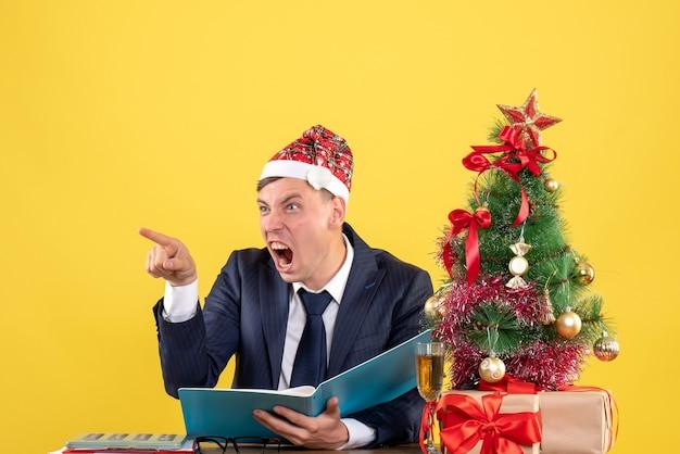 Vista frontal hombre de negocios enojado gritando a alguien sentado en la mesa cerca del árbol de navidad y presenta sobre fondo amarillo