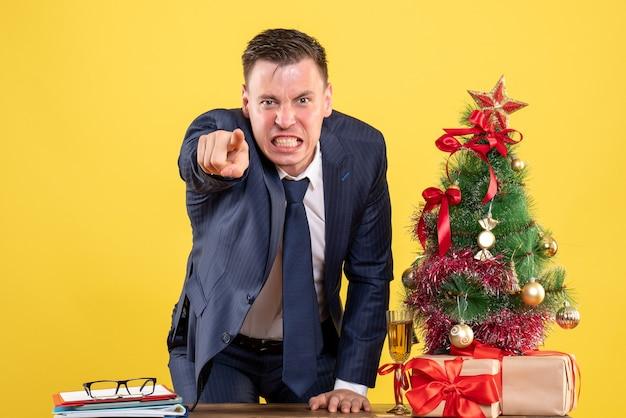 Vista frontal del hombre de negocios enojado de pie detrás de la mesa cerca del árbol de navidad y presenta sobre fondo amarillo